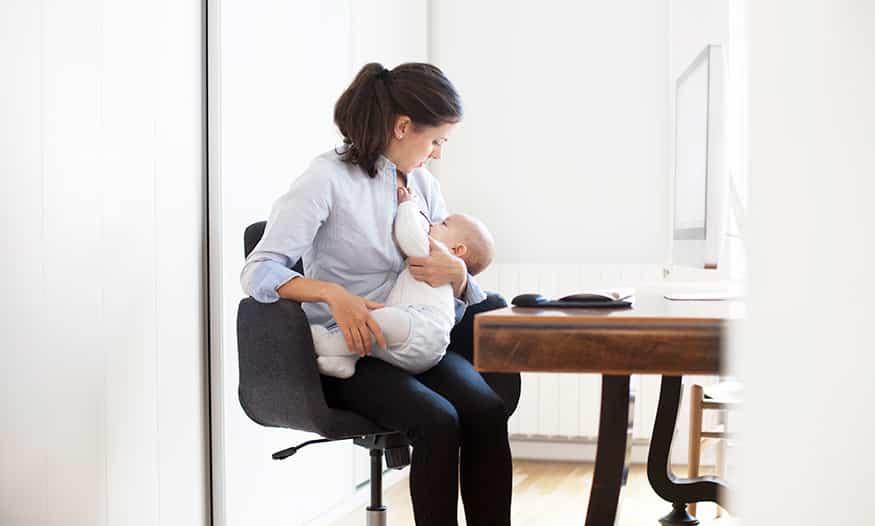 madre amamanta bebé mesa ordenador