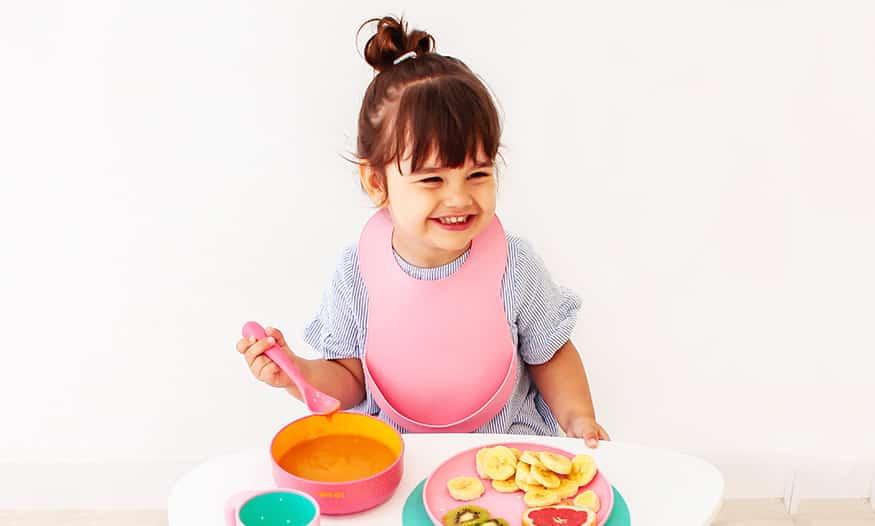 Niña con moño sonríe. Lleva un babero rosa y sujeta cuchara rosa para comer puré en un plato también rosa. En la mesa también hay un plato rosa con plátano, kiwi y pomelo en rodajas.