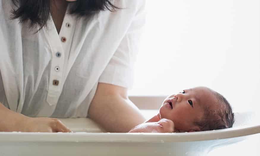 mamá sujeta a bebé dentro de la bañera